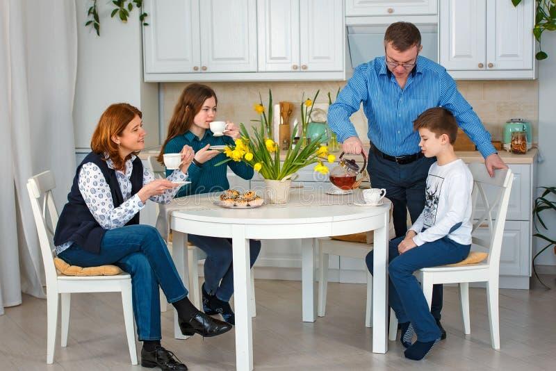 Freundliches family Die helle Teeschale mit einem heißen Getränk Vater gießt Tee stockfotografie