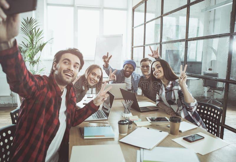 Freundliches frohes Team fotografiert sich lizenzfreie stockfotografie