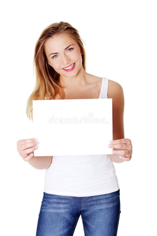 Freundliches jugendlich Mädchen, das unbelegtes Weißbuch anhält stockbilder