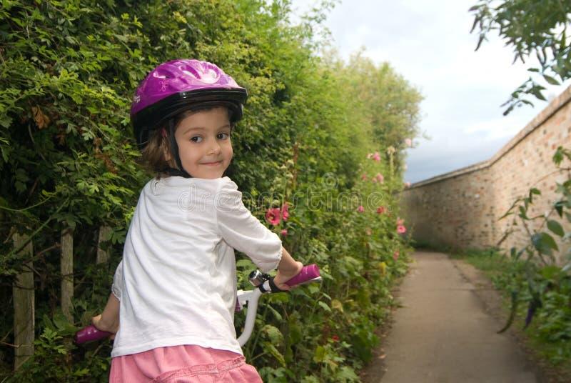 Freundliches Mädchen, das ein Fahrrad reitet stockbild