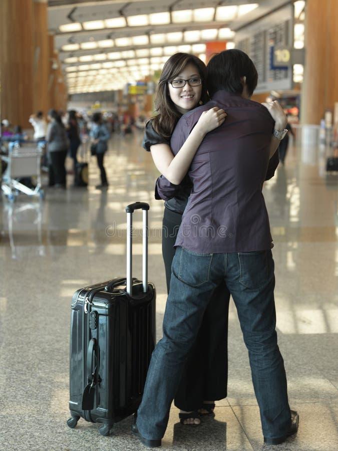 Freundliches Mädchen des asiatischen chinesischen Kerls am Flughafen lizenzfreie stockfotos