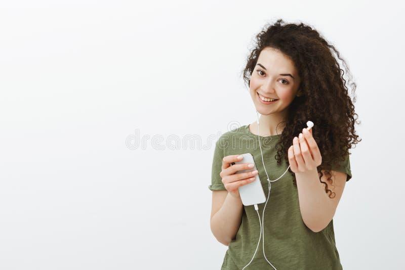 Freundliches Mädchen möchten Musik mit uns teilen Porträt der sorglosen frohen gelockten Frau, breit lächelnd und hält lizenzfreies stockfoto