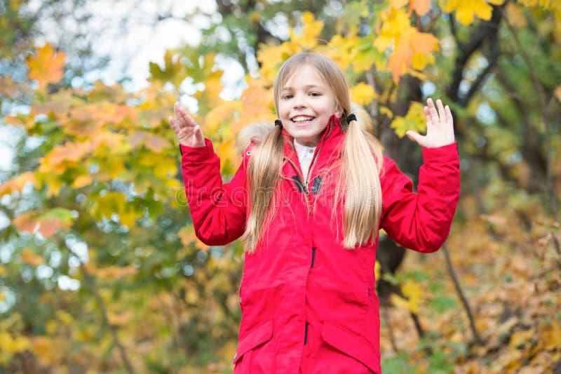 Freundliches Schulmädchen Kinderblondes langes Haar, das in die warme Jacke im Freien geht Das Mädchen, das im roten Mantel glück stockbilder