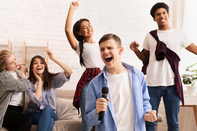 Freundschaft und Heimunterhaltung Teens singt Karaoke stockbilder