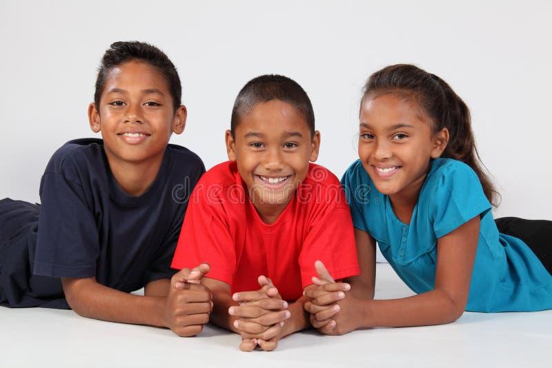 Freundschaft von drei glücklichen ethnischen Schulkindern lizenzfreie stockbilder