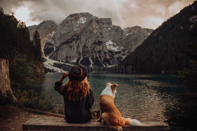 Freundschaft zwischen dem Kind und Hund, die nahe dem See Lago di Braies sitzen stockbild