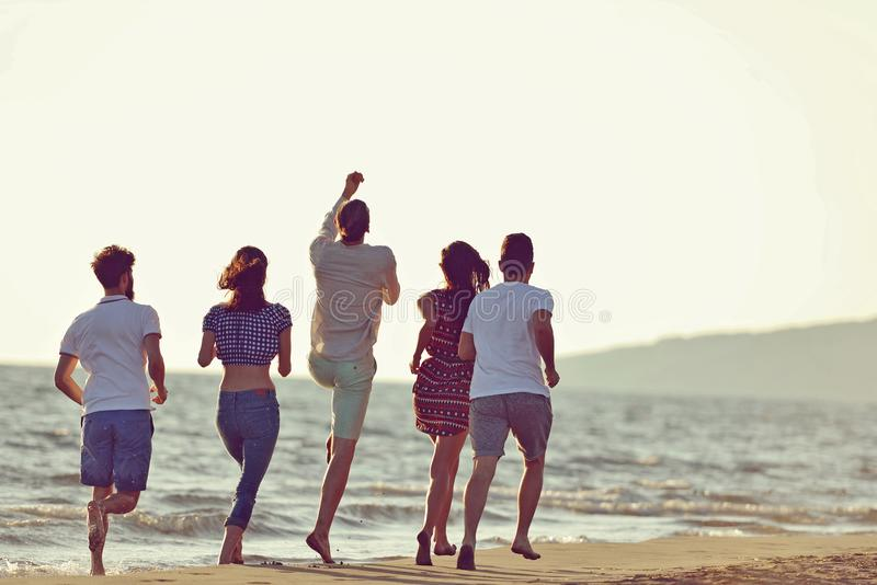 Freundspaß auf dem Strand unter Sonnenuntergangsonnenlicht stockfoto