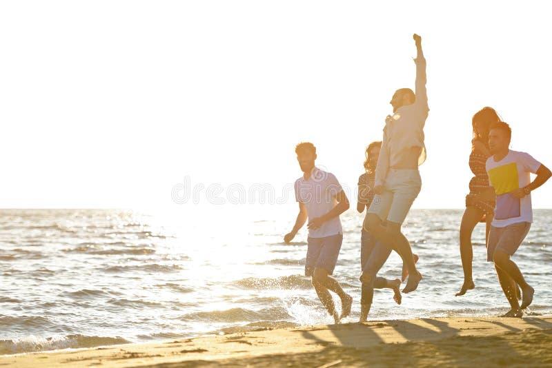 Freundspaß auf dem Strand unter Sonnenuntergangsonnenlicht stockfotografie