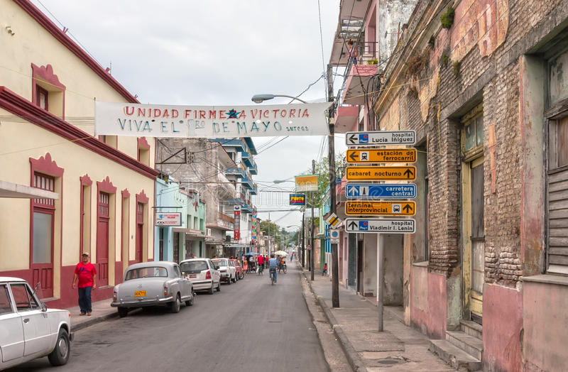 Frexes street with locals, cars, stret signs and streamer. HOLGUIN, CUBA - MAY 1: Frexes street with locals, cars, stret signs and streamer dedicated to 1 de stock photo