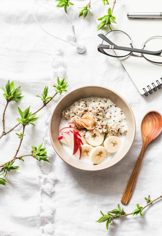 Fri frukost för vegetarisk gluten - quinoaen, kokosnöt mjölkar, bananen, äpplet, bunke för jordnötsmör på ljus bakgrund, bästa si fotografering för bildbyråer