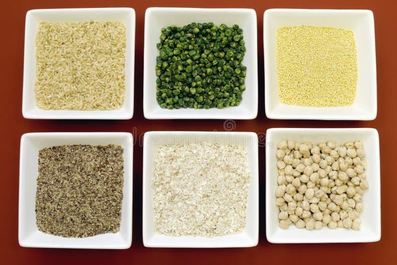 Fri kornmat för Gluten - råris, millet, LSA, boveteflingor och chickpeas och gräsplanärtalegumes - flyg- närbild. arkivbild