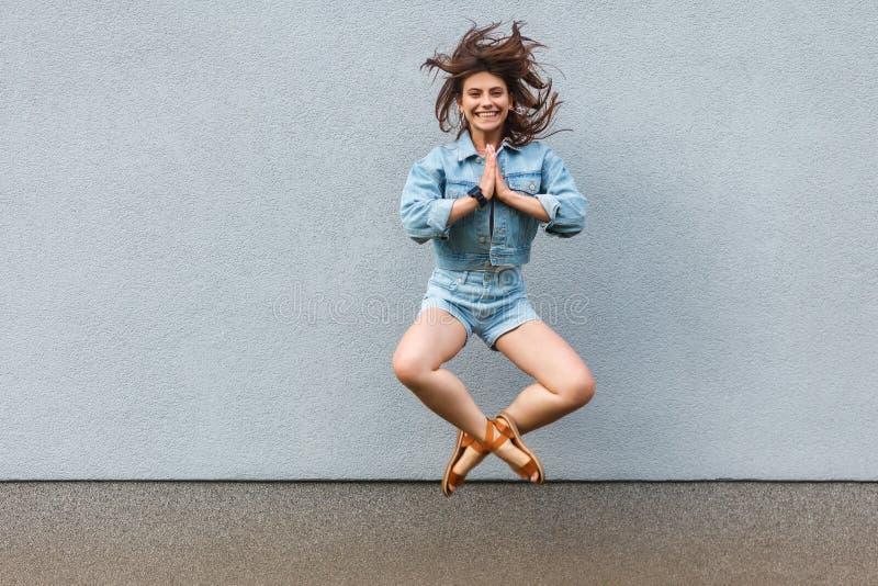 Fri lycklig härlig kvinna i tillfällig jeansgrov bomullstvillstil i sommartid som hoppar på ljust - den blåa väggen med namaste g royaltyfri bild