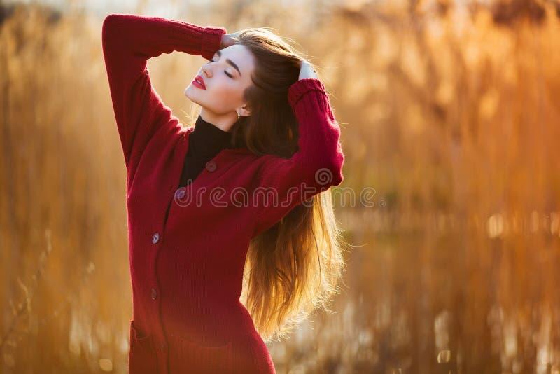 Fri lycklig ung kvinna Den härliga kvinnlign med långt sunt blåsa hår som tycker om solljus parkerar in, på solnedgången Vår royaltyfria foton