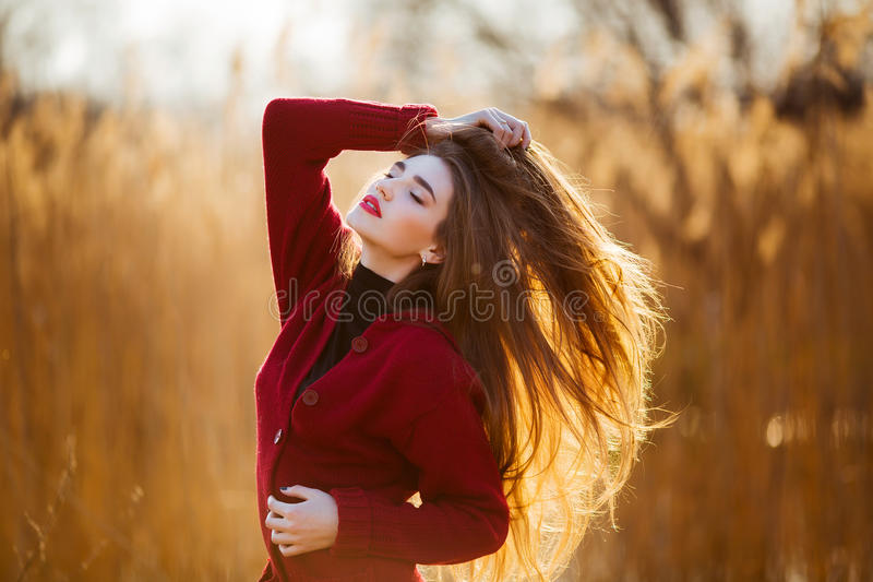 Fri lycklig ung kvinna Den härliga kvinnlign med långt sunt blåsa hår som tycker om solljus parkerar in, på solnedgången Vår royaltyfri bild