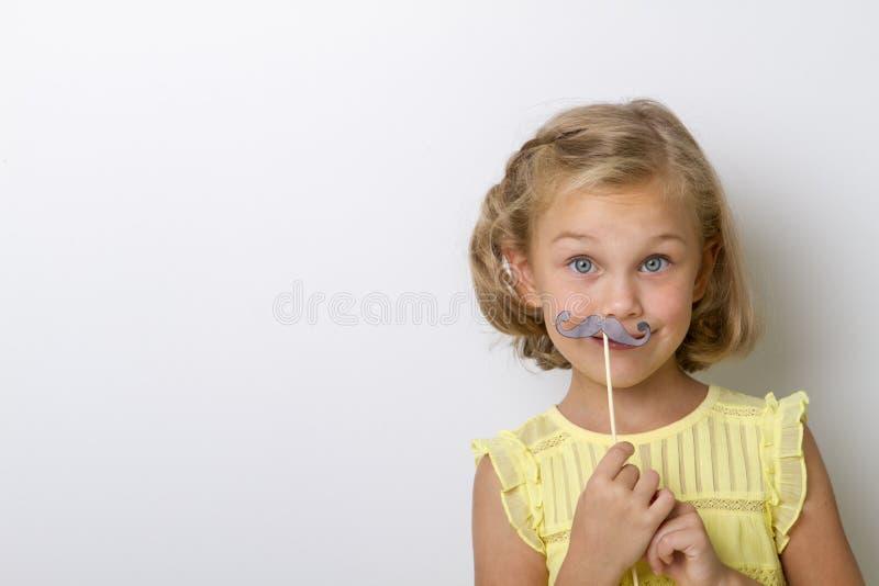 Fri tid för gyckel Stäng sig upp ståenden som den lilla flickan med fejkar mustaschen med duns arkivfoto