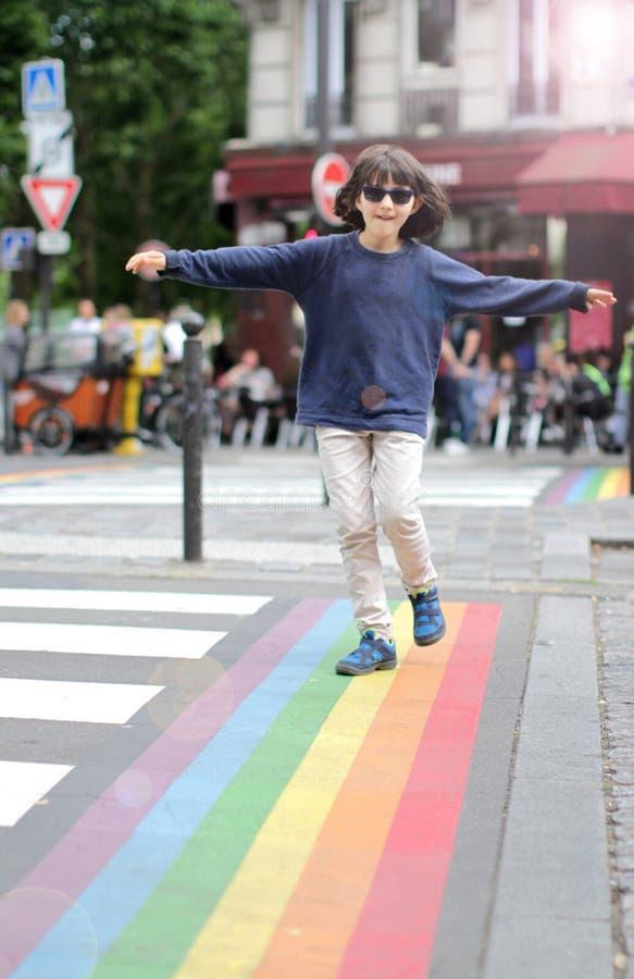 Fri ung pojke med solglasögon som går till och med det glade symbolet arkivfoto