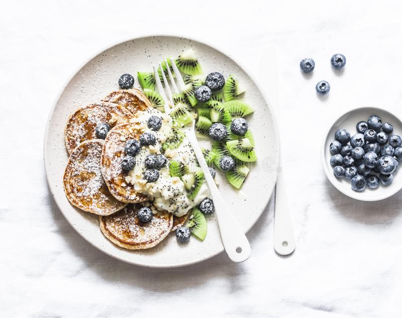 Fria pannkakor för gluten med den kokosnötyoghurt, kiwin och blåbär på en ljus bakgrund arkivfoto