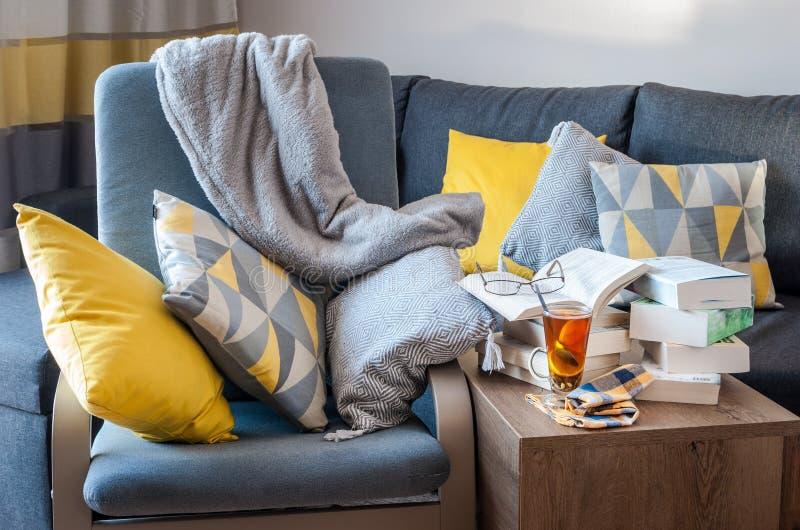 Fria Tid med dina favoritböcker och ett exponeringsglas av varmt te royaltyfri foto