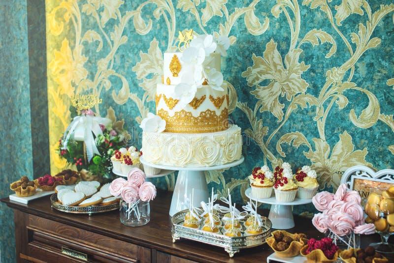 Friandise l'épousant de luxe avec un beau gâteau blanc décoré des ornements d'or Concept des desserts chics de mariage images libres de droits