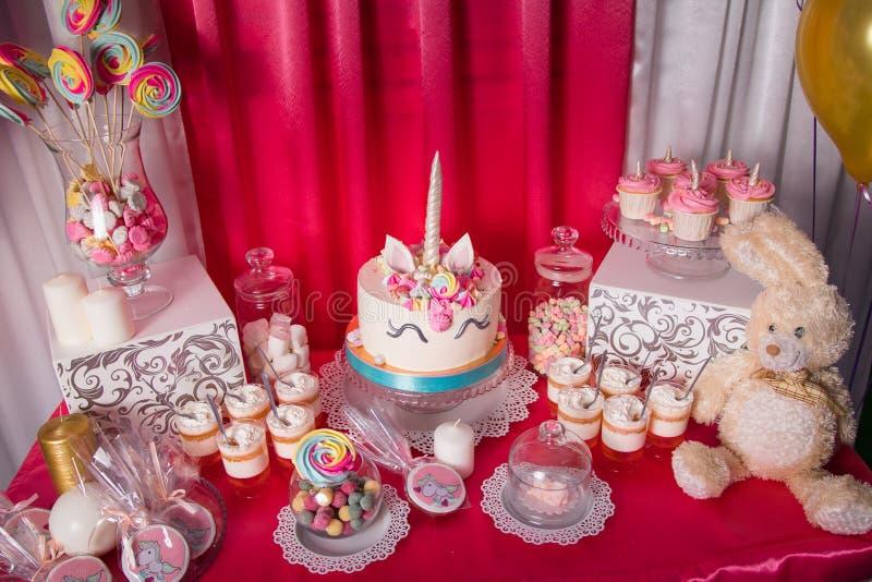 Friandise pour le premier anniversaire pour le petit bébé Table douce et grand gâteau de licorne image stock