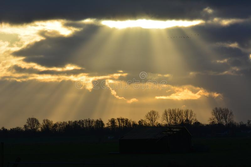 View at Waverveen in the netherlands. On a friday morning in january, the sunbeams coming through the clouds location: Waverveen in the Netherlands royalty free stock photo