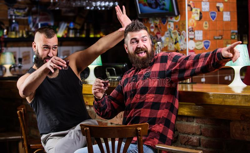 Friday relax in pub. Cheers concept. Hipster brutal bearded man drinking alcohol with friend at bar counter. Men drunk. Friday relax in pub. Cheers concept royalty free stock image