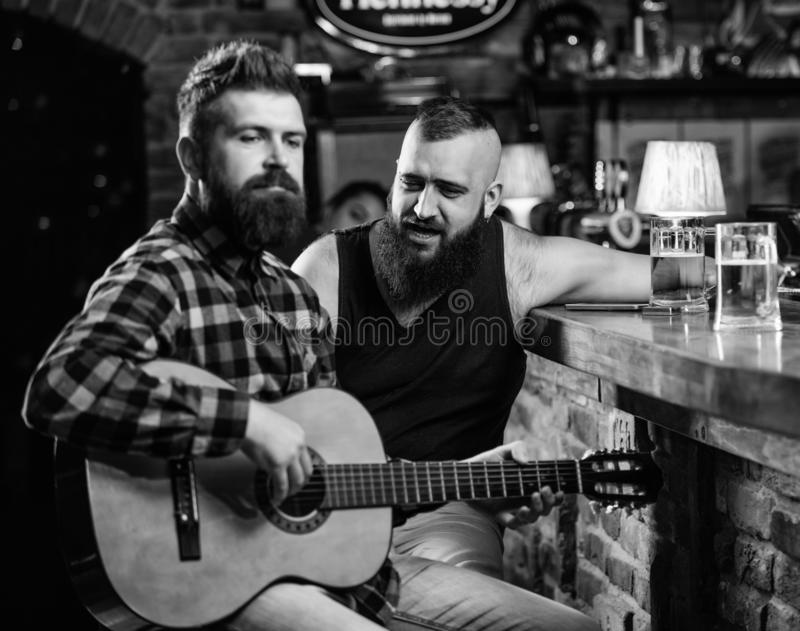 Friday relaxation in bar. Friends relaxing in bar or pub. Real men leisure. Hipster brutal bearded spend leisure with. Friend in bar. Man play guitar in bar royalty free stock photography