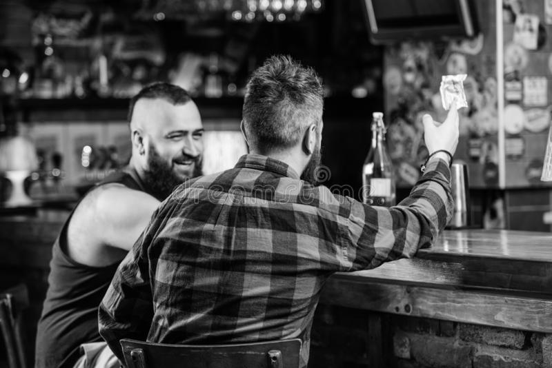 Friday relaxation in bar. Friends relaxing in pub. Hipster brutal bearded man spend leisure with friend at bar counter. Friday relaxation in bar. Friends stock photography