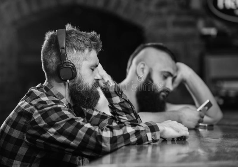 Friday relaxation in bar. Hipster bearded man spend leisure at bar counter. Order drinks at bar counter. Men with. Friday relaxation in bar. Hipster bearded men royalty free stock image