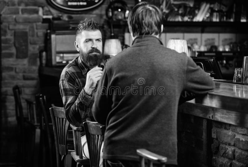 Friday relaxation in pub. Friends relaxing in pub. Friendly conversation with stranger. Hipster brutal bearded man spend. Friday relaxation in pub. Friends royalty free stock photography