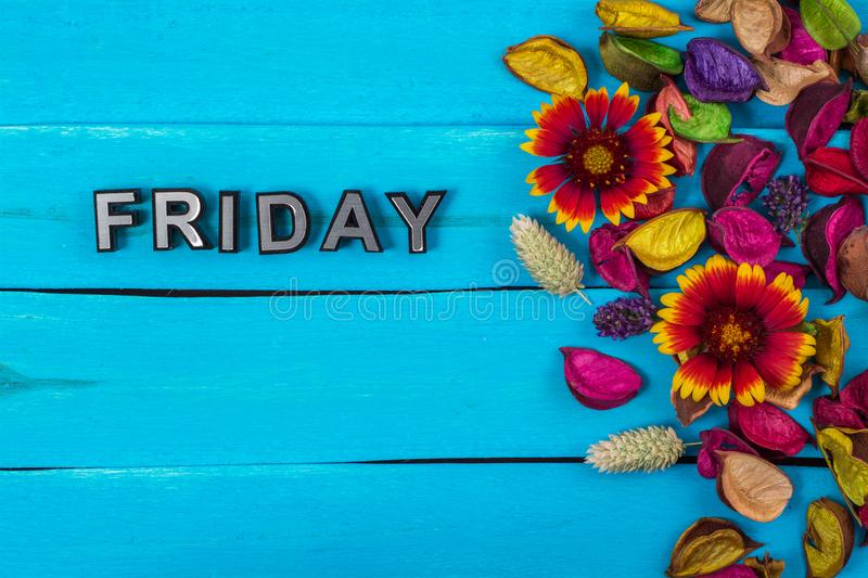 Friday word on blue wood with flower stock images