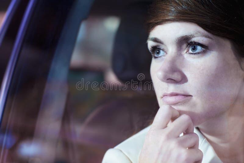Fridfull affärskvinna med handen på hakan som ser till och med bilfönstret på stadsutelivet, reflekterade ljus royaltyfri fotografi