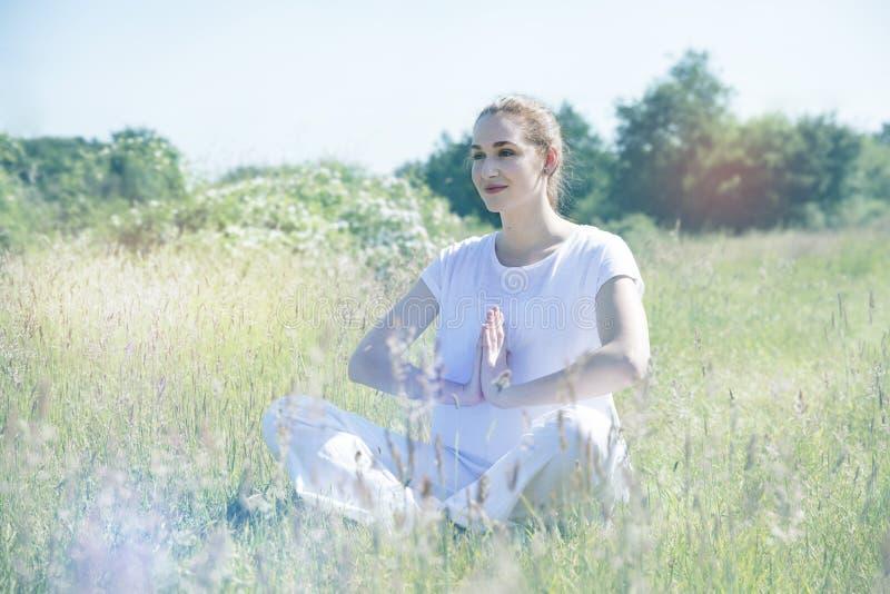Fridfull härlig andning och meditera för yogaflicka som korsa-läggas benen på ryggen arkivbilder