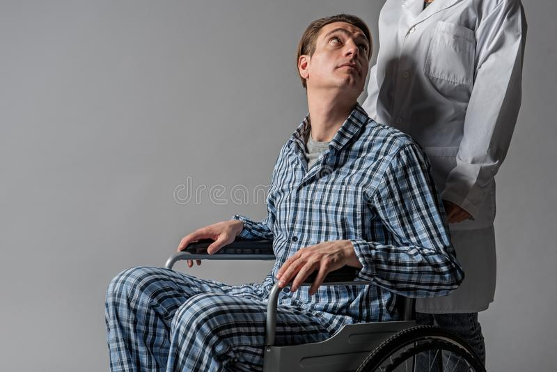 Fridfull rörelsehindrad man som stirrar på sjuksköterskan arkivfoton