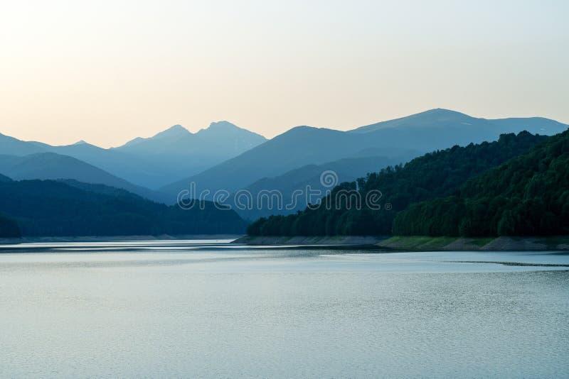 Fridfull sjö på solnedgången royaltyfri foto