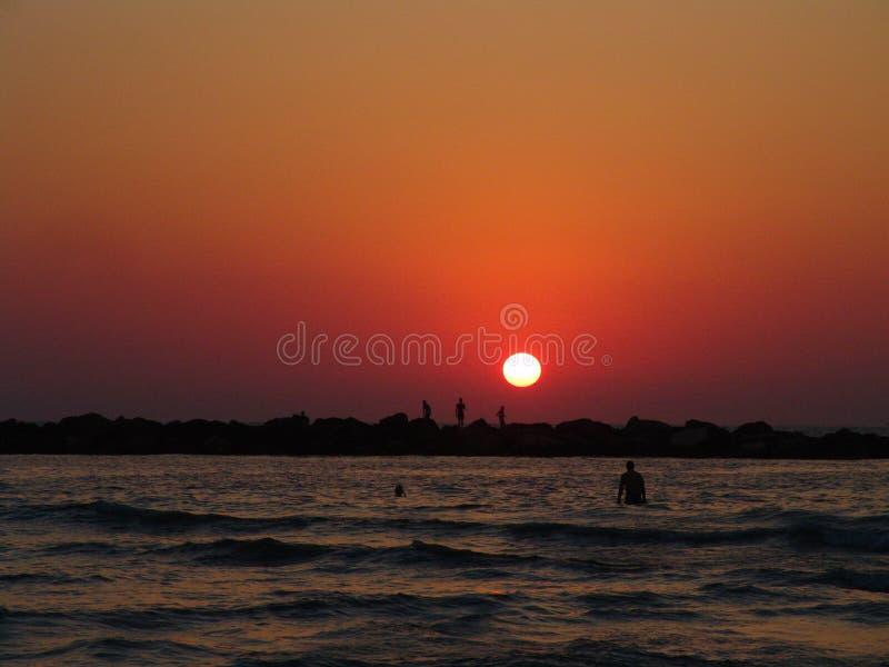 Fridfull sommarsolnedgång över den Tel Aviv havsstranden, i livliga orange färger med konturer av folk som simmar, fiskar och går fotografering för bildbyråer