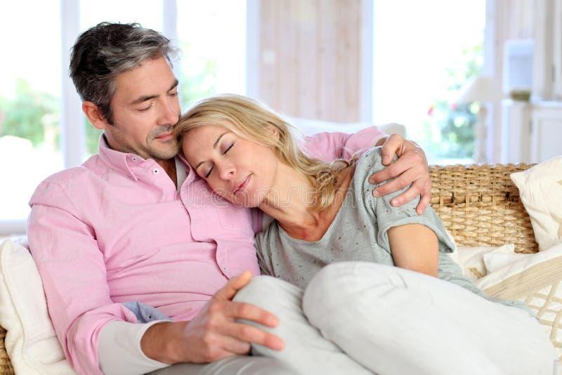 Fridfulla par som kopplar av i soffa arkivfoto