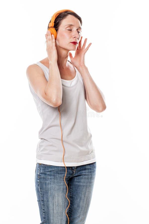 Fridfullt kvinnaanseende, i att lyssna till musik på hörlurar arkivfoto