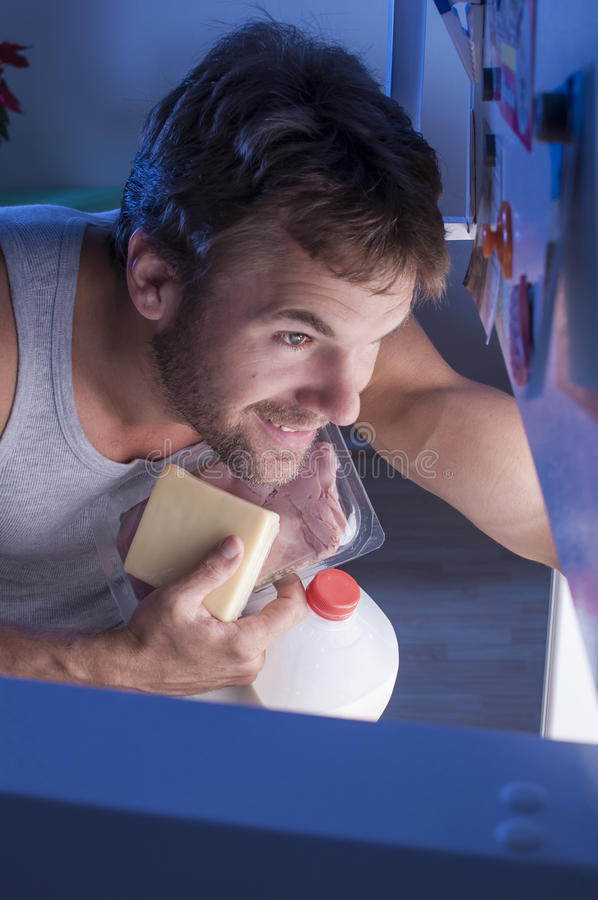 Fridge raid. Hungry man raids refridgerator at night collecting milk, ham, and cheese to eat