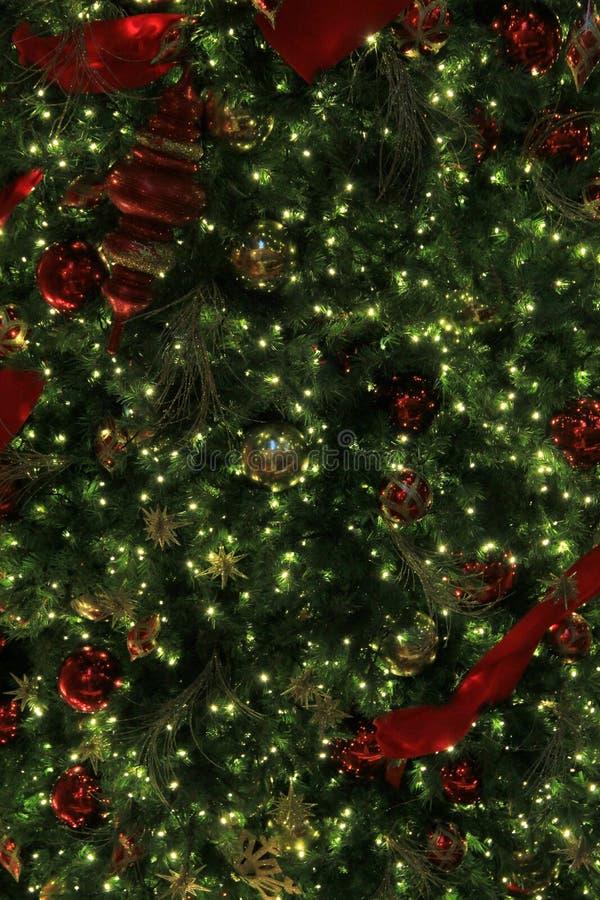Fridsam bakgrund av julgranen med röda och guld- garneringar arkivfoto