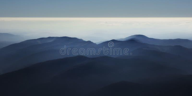 Fridsam blå naturbakgrund med dimmiga Bucegi berg i Carpathians, Rumänien royaltyfria foton