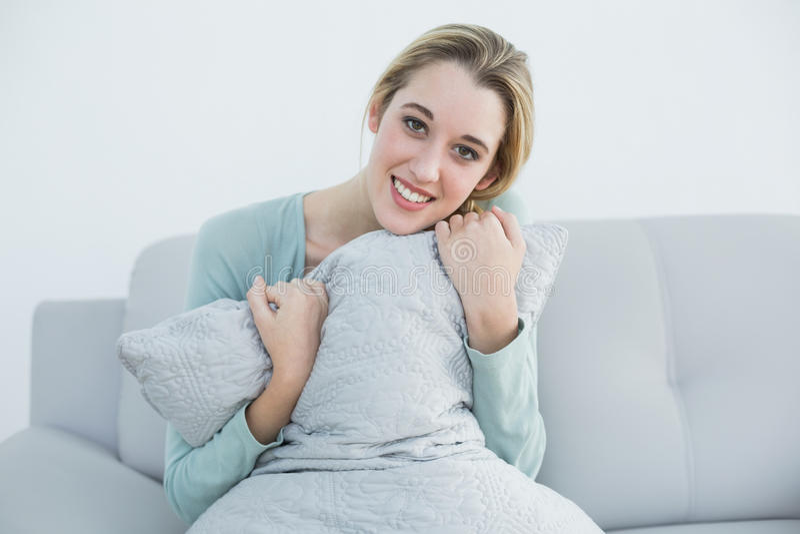 Fridsam blond kvinna som rymmer ett kuddesammanträde på soffan arkivfoto