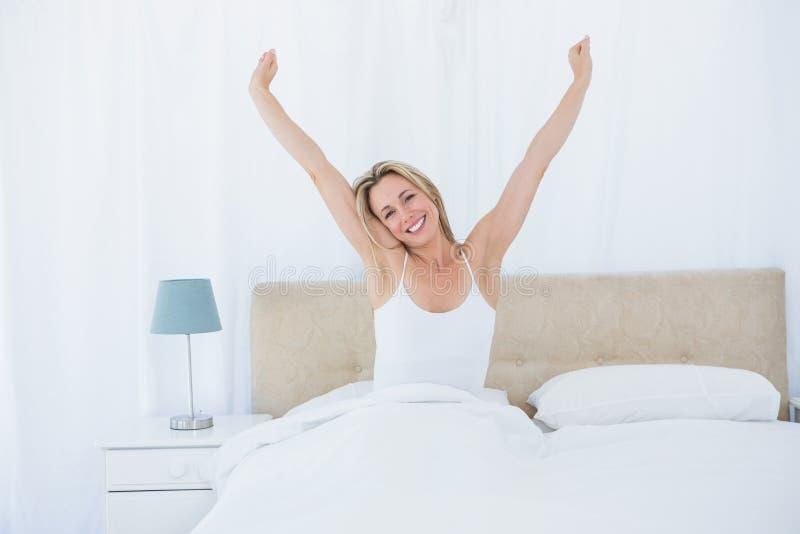 Fridsam blond kvinna som sträcker i säng royaltyfri bild