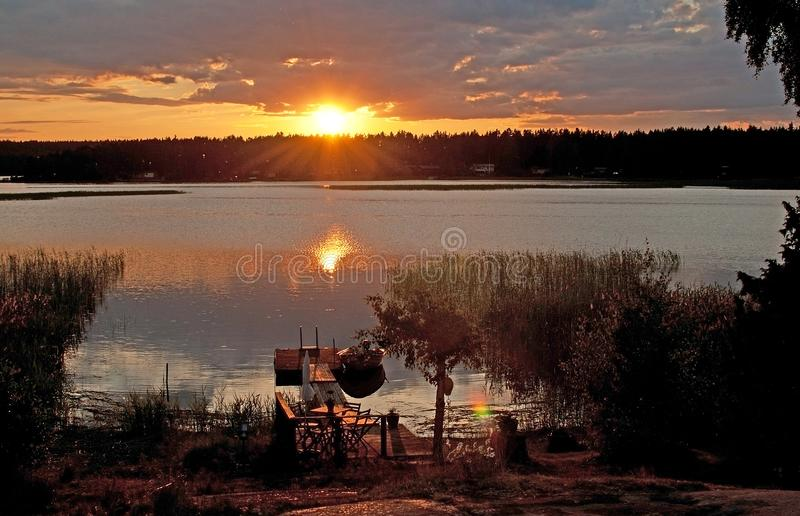 Fridsam färgrik solnedgång och fartyg vid en sjö royaltyfria bilder