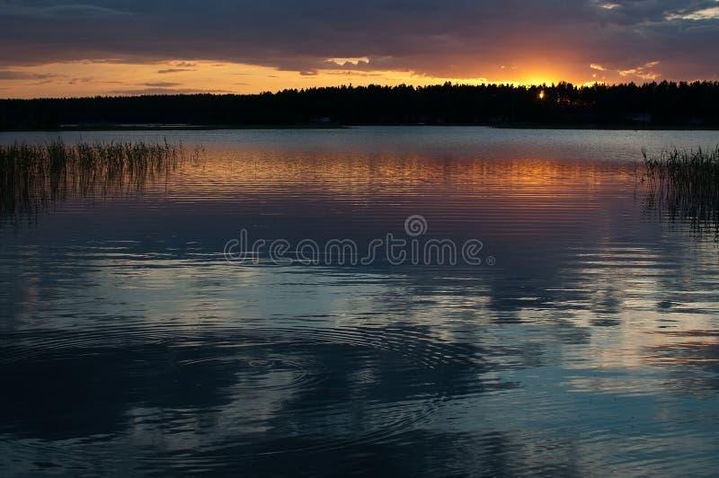 Fridsam färgrik solnedgång vid en sjö med himmelreflexioner royaltyfri foto