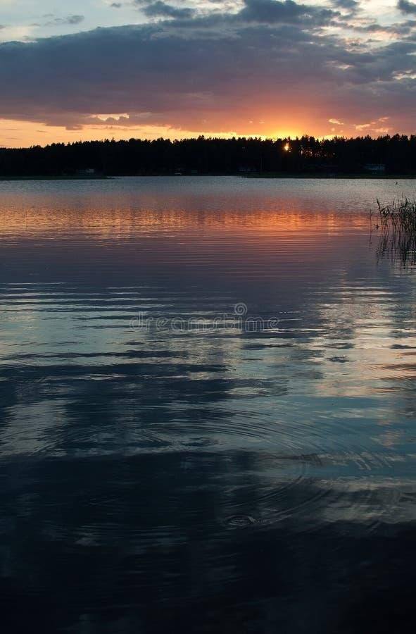 Fridsam färgrik solnedgång vid en sjö med himmelreflexioner royaltyfri fotografi
