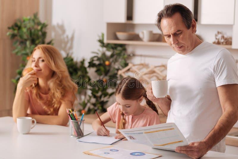Fridsam familj som hemma tycker om morgon royaltyfri fotografi
