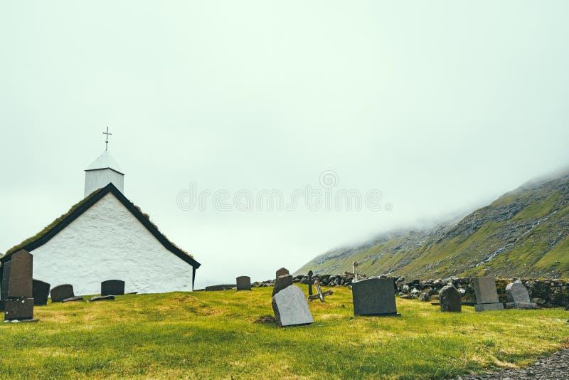 Fridsam gammal kyrka med dimma i Saksun med kopieringsutrymme, Faroe Island, norr Atlantic Ocean, Europa, gömd ädelstenloppdestin royaltyfri foto