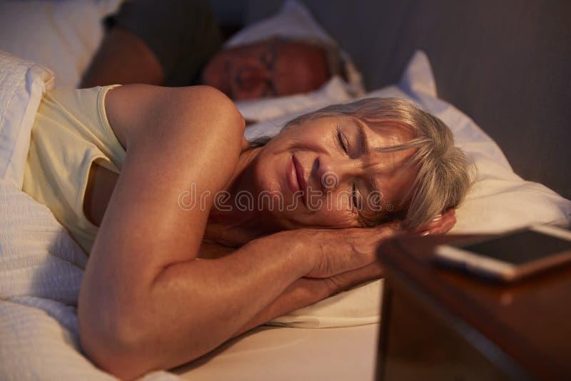 Fridsam hög kvinna sovande i säng på natten arkivbild