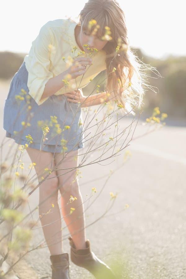 Fridsam hipsterflicka som luktar blommor royaltyfria foton